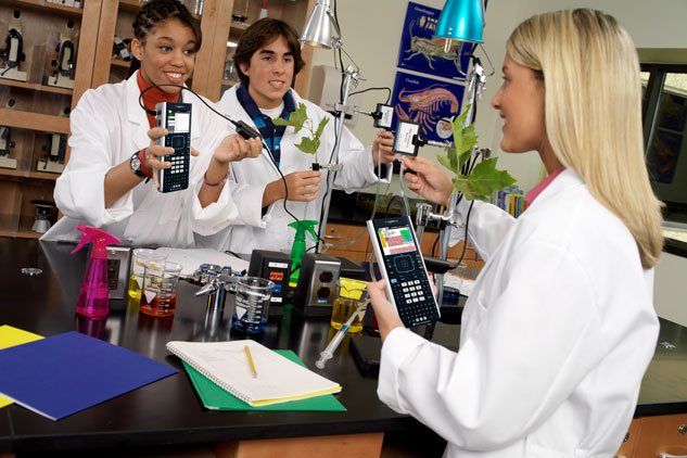 Three students using calculators around a lab table