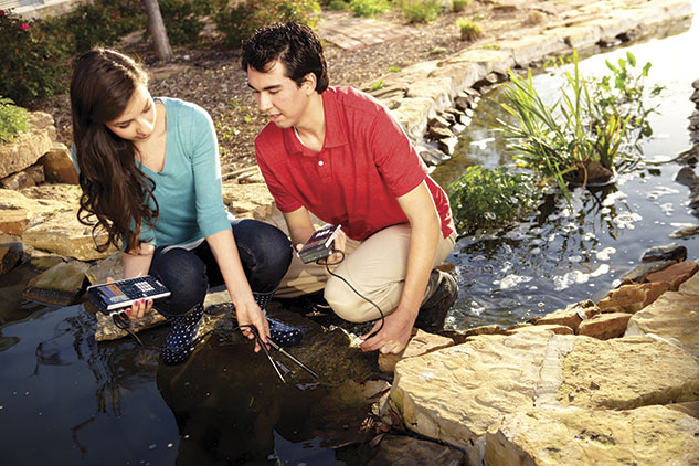Two students using calculators and data collection sensors at a pond