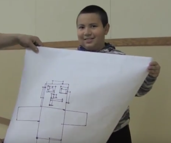 A Keota elementary school 3rd grader shares his robot drawing with his classmates.